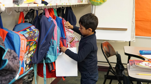 Boy putting items in backpack