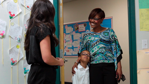 Teacher greets a student and a parent