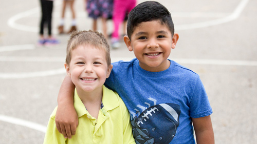 Two students smiling at recess
