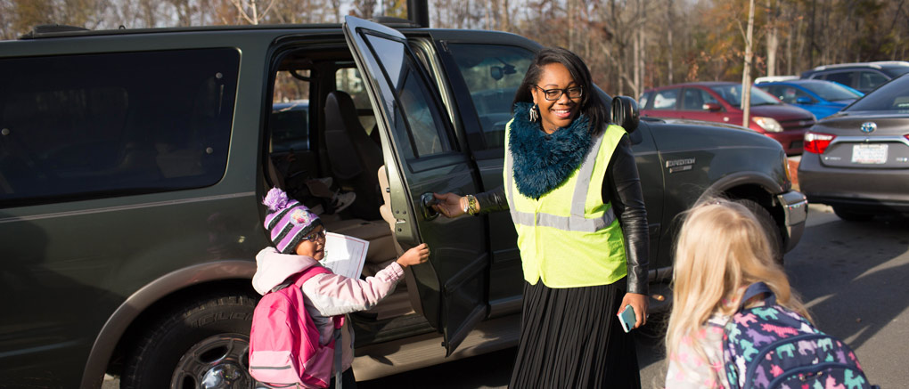 Teacher assisting arriving students