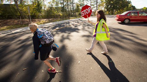 Crossing guard helping student